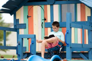 Young boy sitting reading on a wooden playground