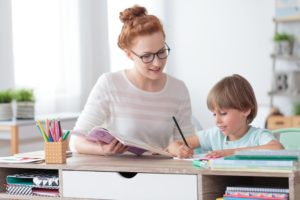 Mom with glasses helping son with schoolwork