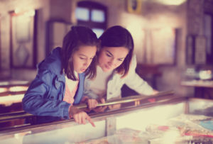 Mother and daughter examining item at museum