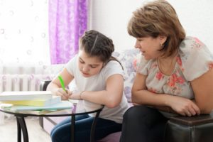 A mother and daughter work on homework.
