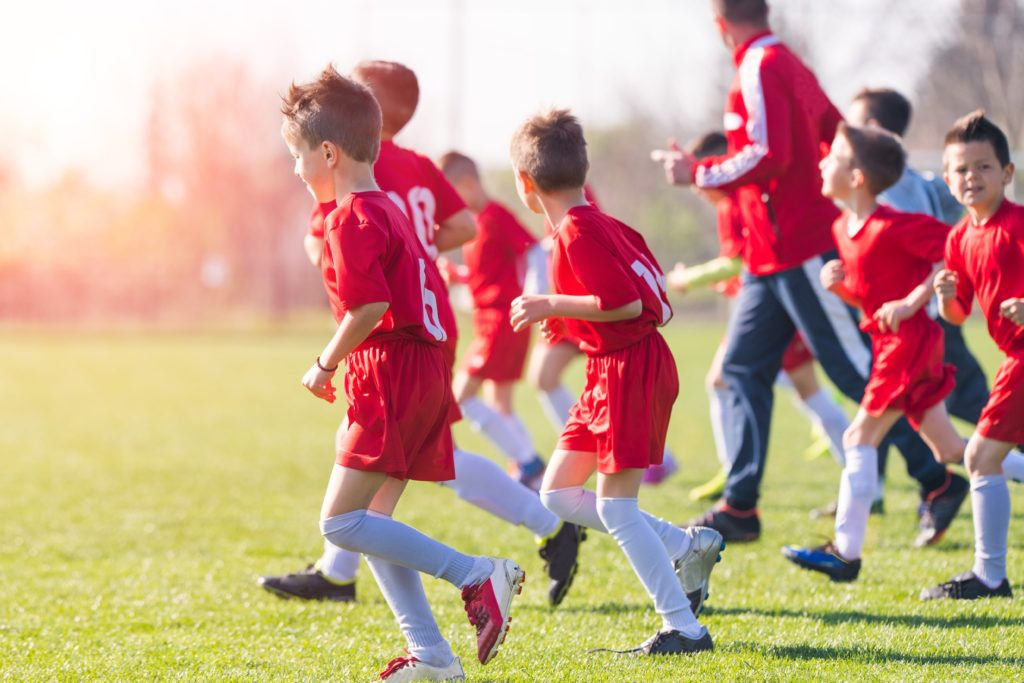 Young soccer players run onto the field with their coach.