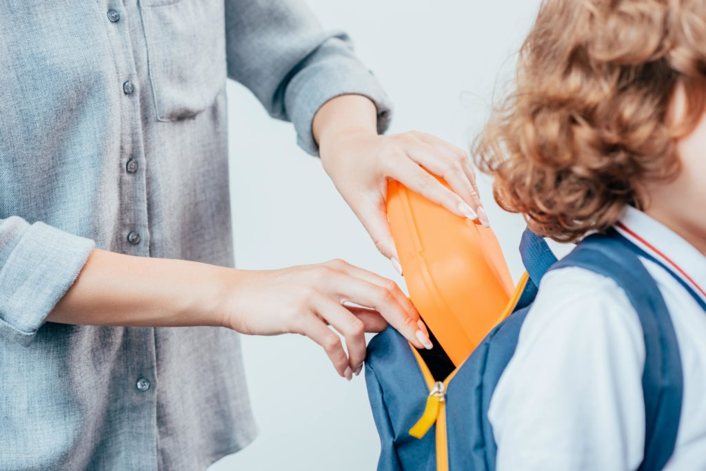 Mom putting lunch in student's backpack