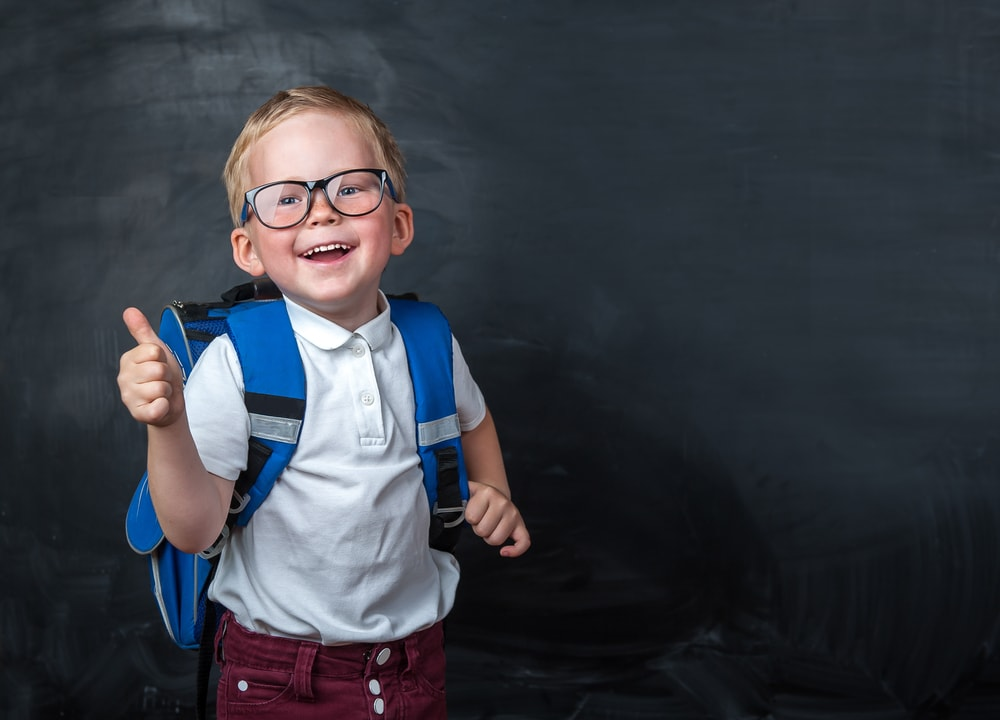 Happy smiling boy with glasses and backpack giving a thumbs up