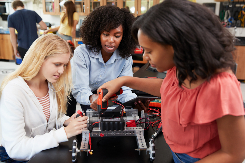 Teacher with robot teaching two middle school girls