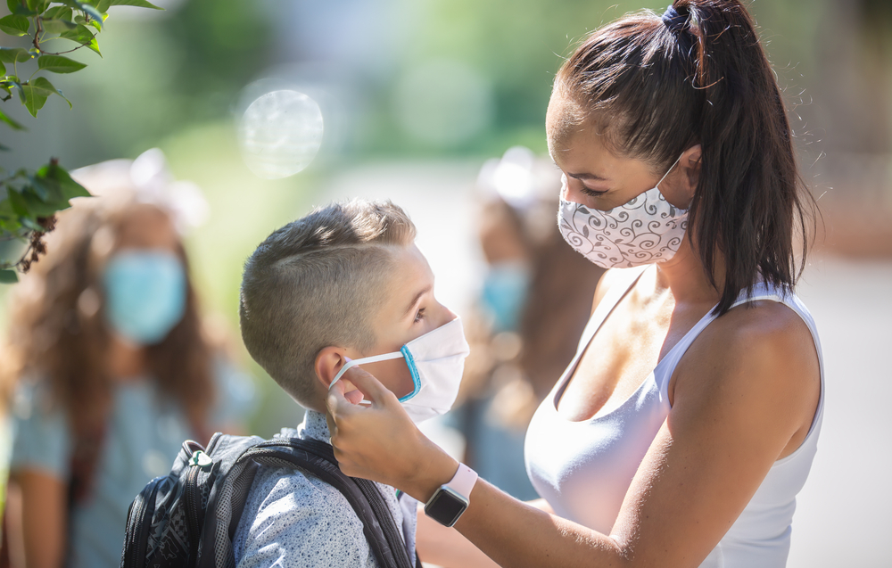Masked boy with mother getting ready for school