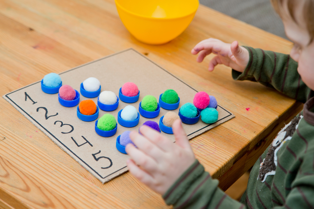 Boy learning math with colored pom poms