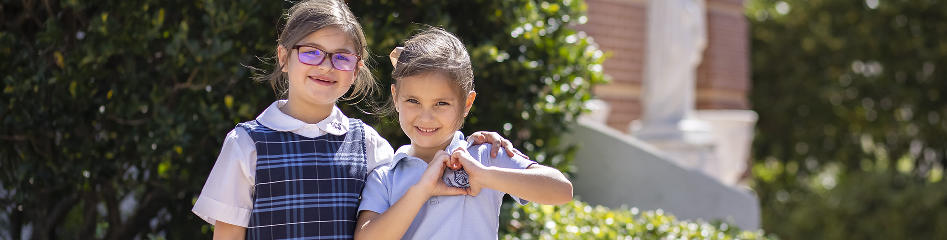 two young female girls in blue checked uniforms with white shirts smiling at the camera